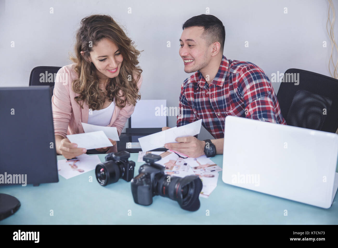 two photographers looking at their photo result after photo sess - Stock Image