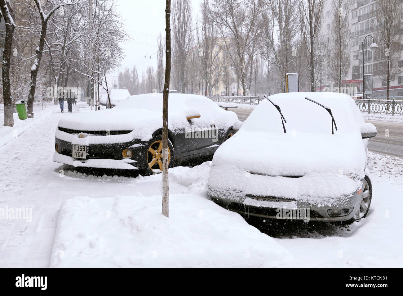 City after blizzard. Cars parked on a street of Kyiv covered with snow. January 12, 2016. Kyiv, Ukraine. - Stock Image