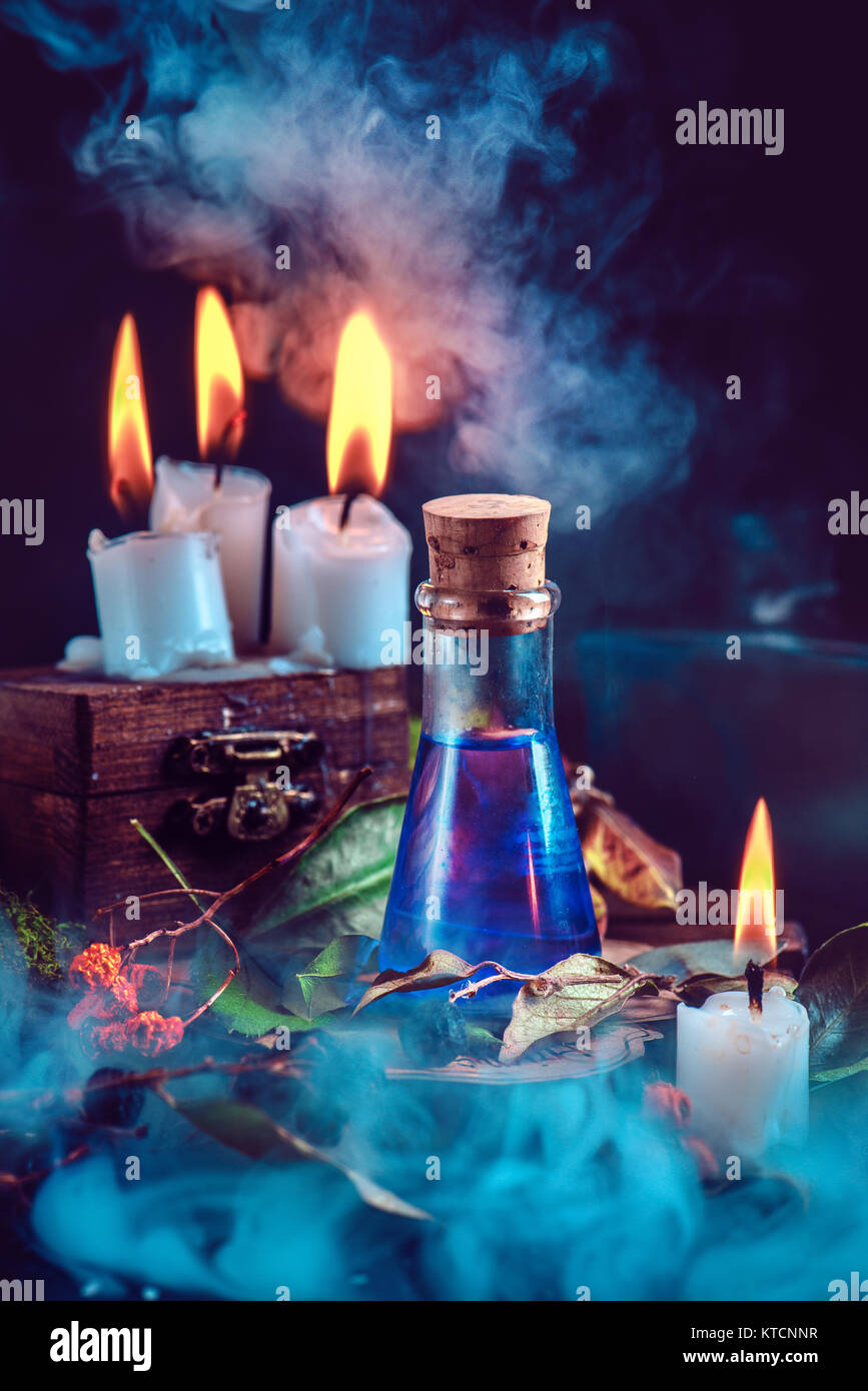 Magical still life with spells, herbs, potion ingredients, wax candles and a glass bottle with mystic liquid on - Stock Image