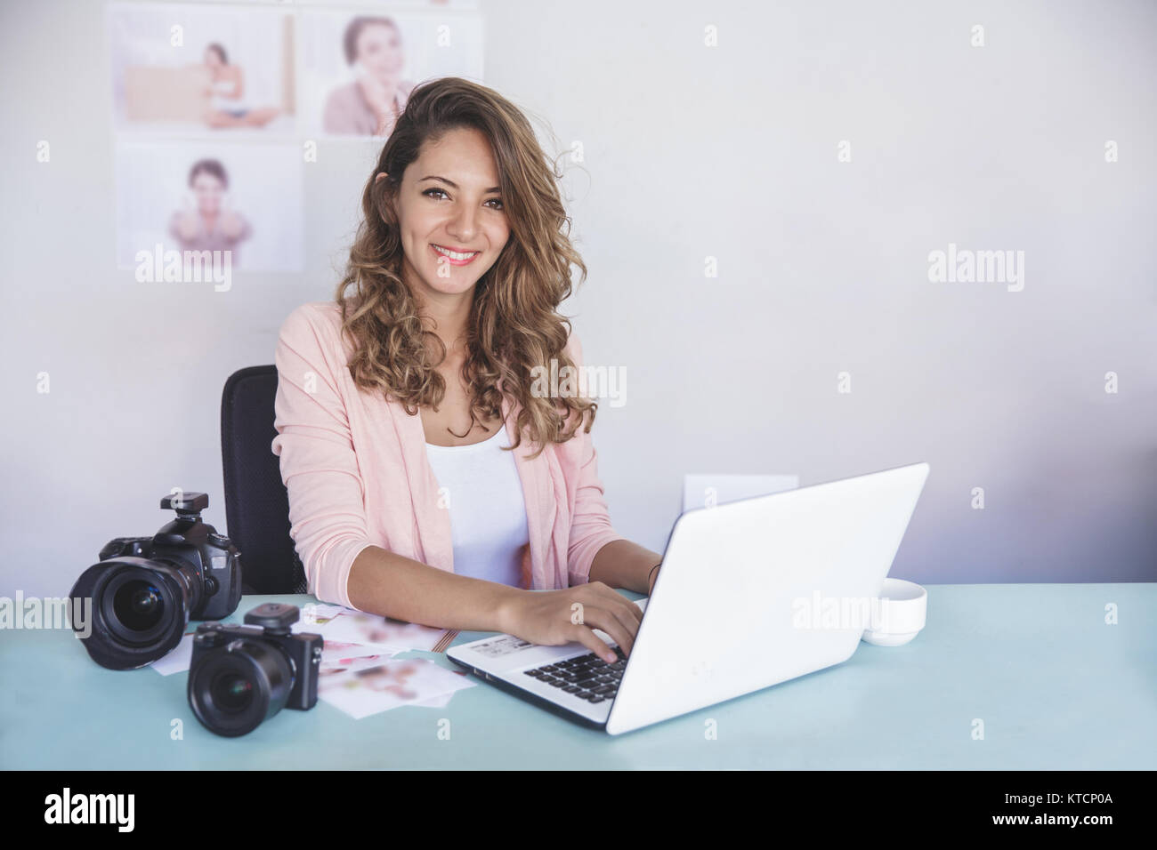 young photographer sitting on her office while working on laptop - Stock Image