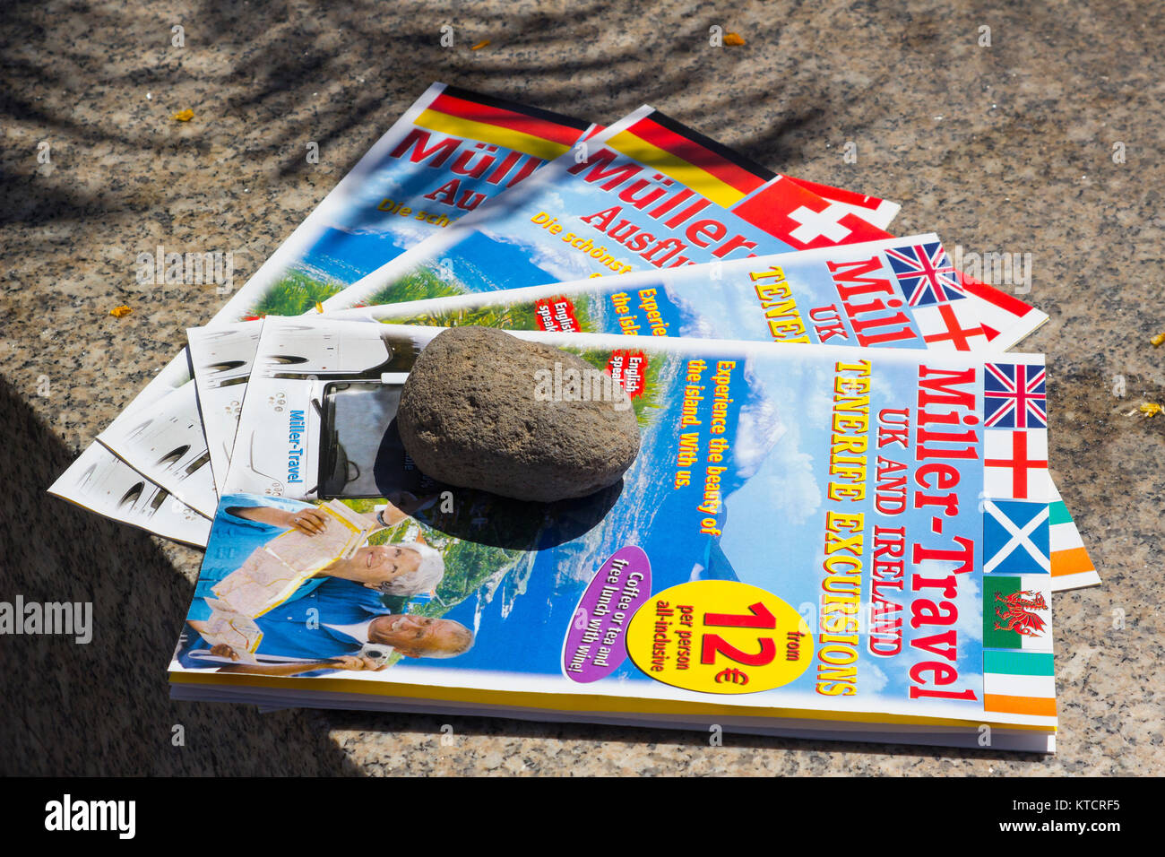 Free to take travel agents brochures laid out on a marble slab in the main street of Playa de las Americas in Tenneriffe - Stock Image