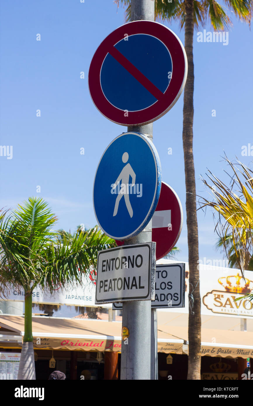 A variety of street signs with highly reflective surfaces on a pole in the Canary Island resort of Playa De Las Stock Photo