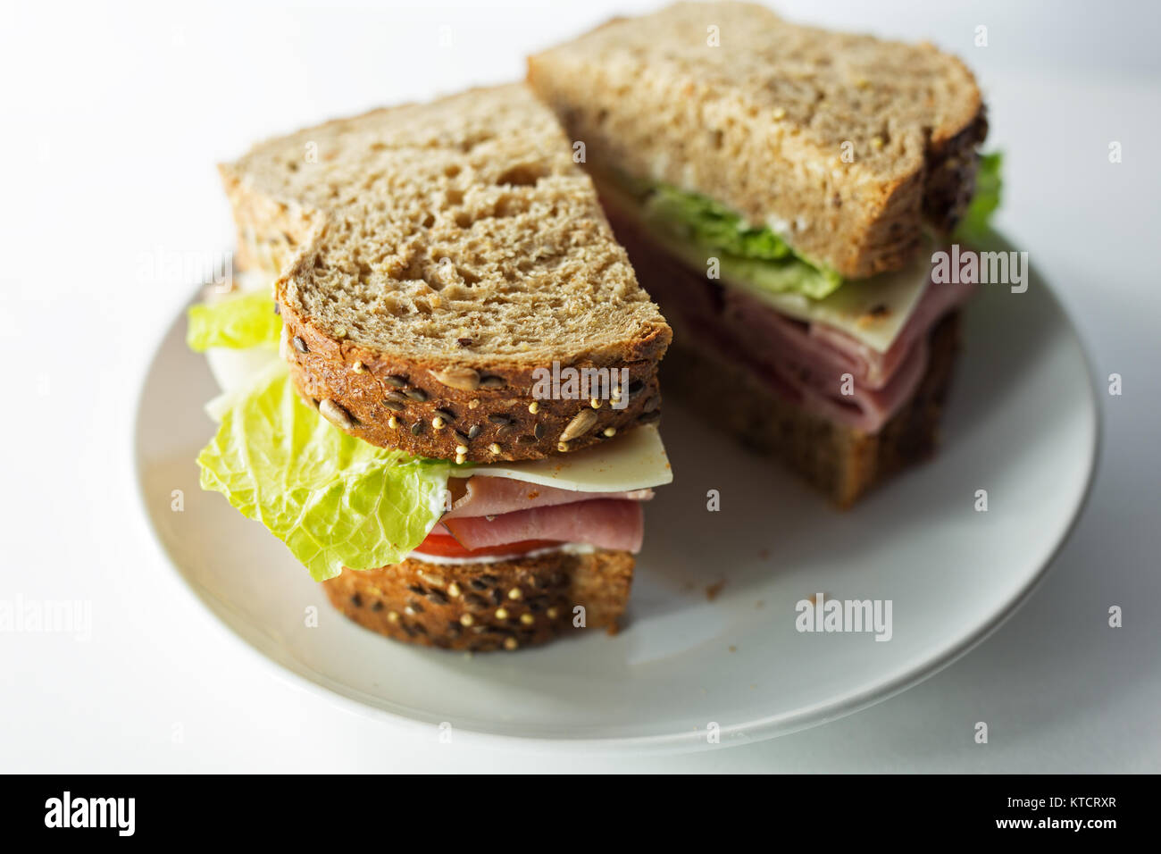 Ham sandwich made with artisan bread on a white plate. Copy space. White background. - Stock Image