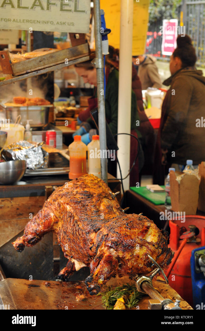a whole pig or hog roasting on a spit at London's borough market. Hog roasts for eating at street food stalls on Stock Photo