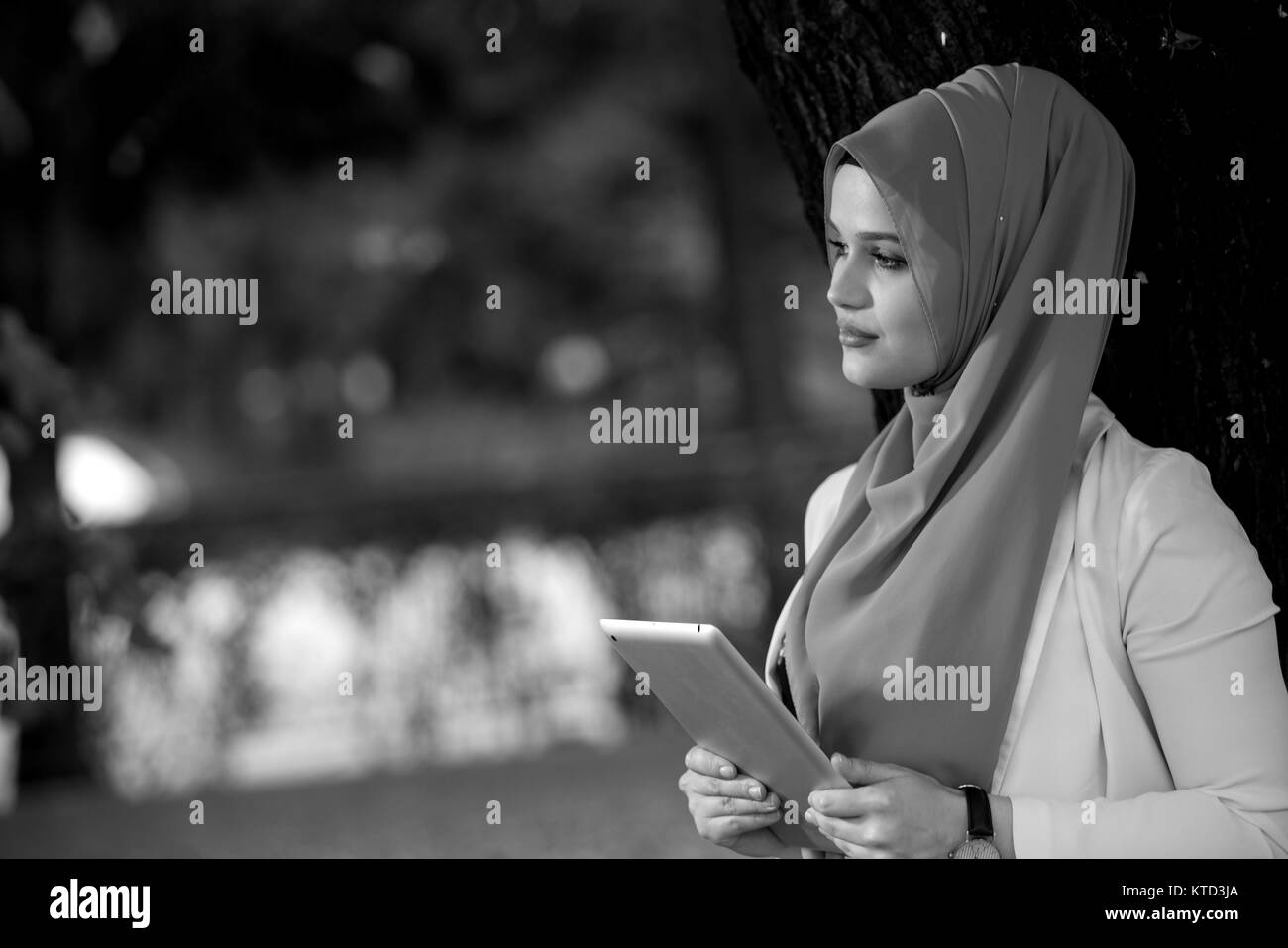 Young girl wearing hijab using talbet outside happy stock image