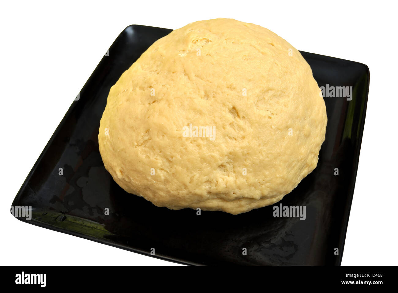 Isolated image of risen yeast dough for bread or pizza in a black baking tray - Stock Image