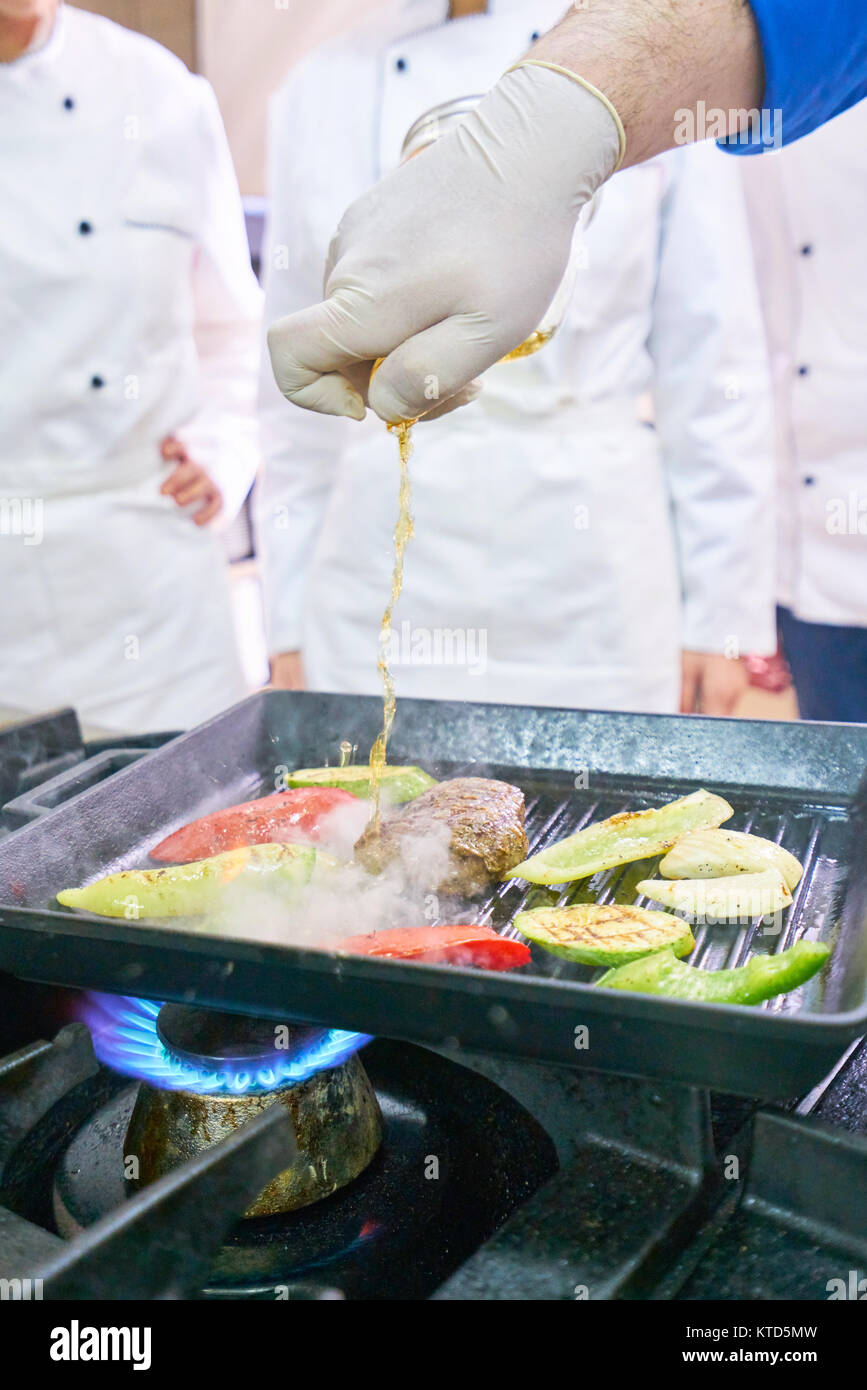 Chef in restaurant kitchen at stove with pan, doing flambe on food ...