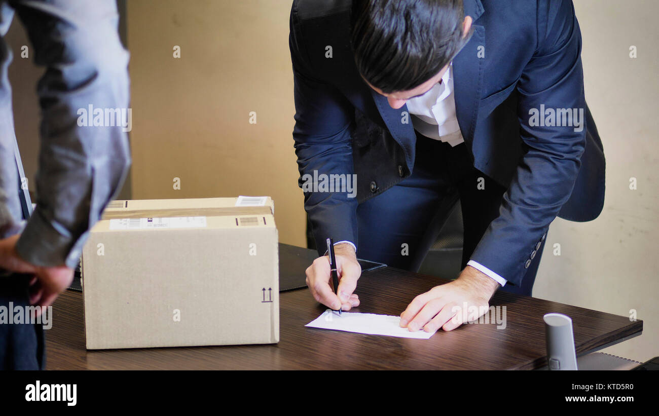 Businessman sitting in his office and looking at parcel delivered him by unrecognizable courier, signing receipt - Stock Image