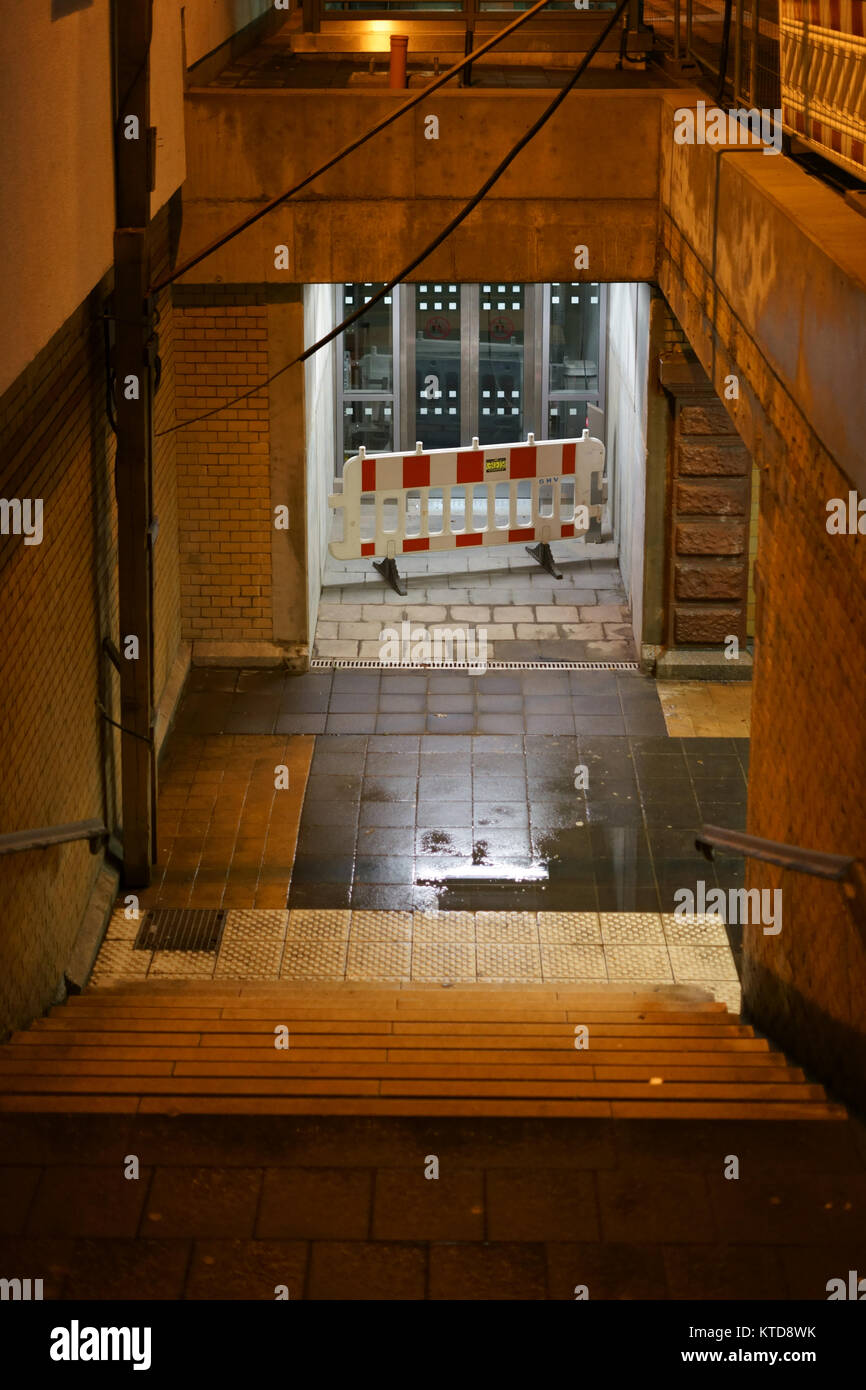The dark steps of a station tunnel with puddles and damp walls. - Stock Image