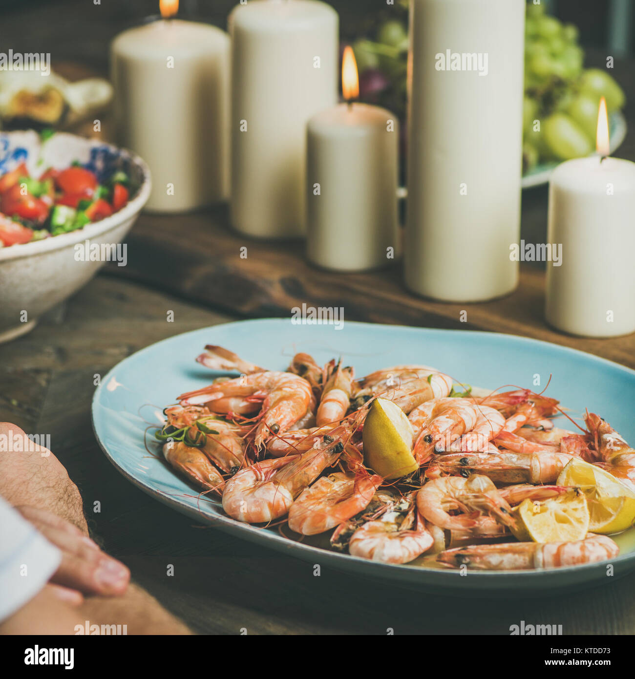 Salad, shrimps and candles on wooden table, square crop - Stock Image