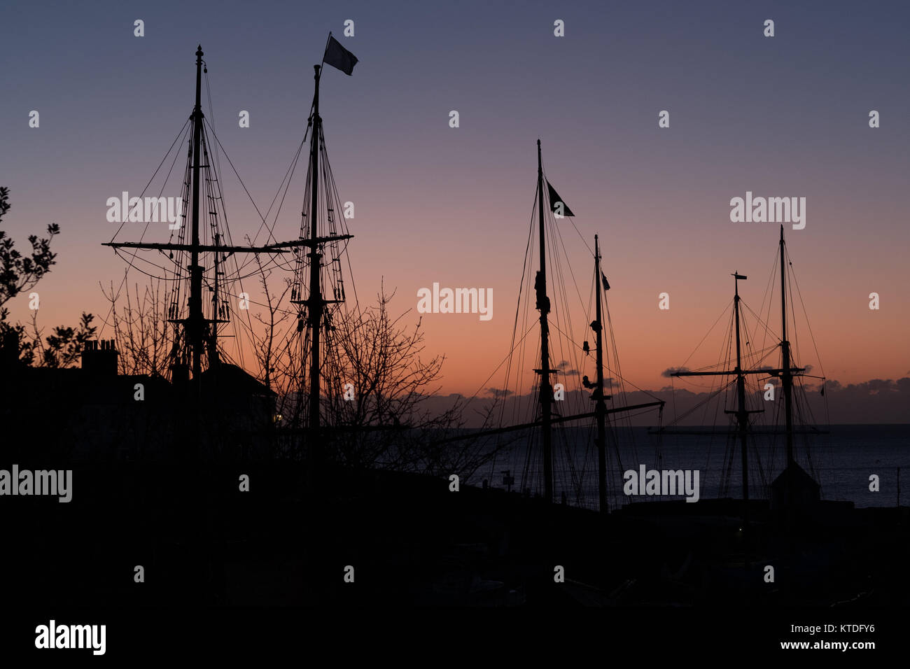 Square rigged tall ships picked in Charlestown, Cornwall, at sunrise - Stock Image