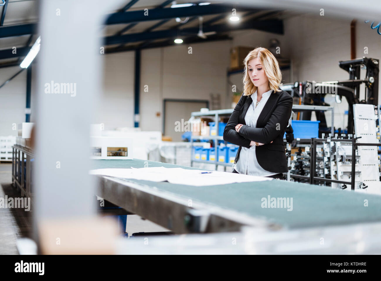 Blond businesswoman standing on shop floor, looking at plans - Stock Image