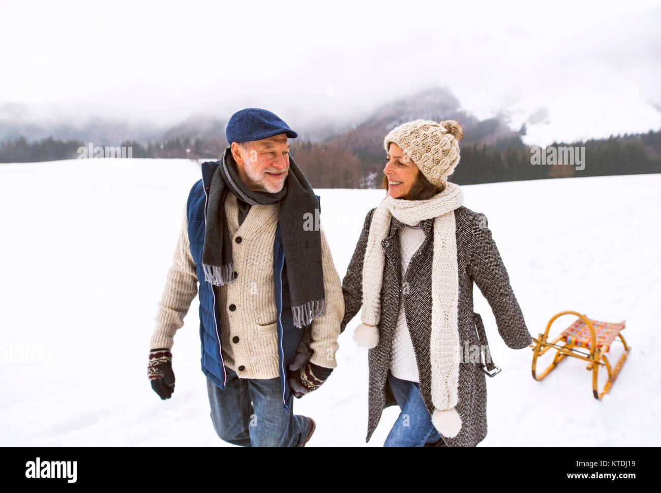 Happy senior couple with sledge walking in snow-covered landscape - Stock Image