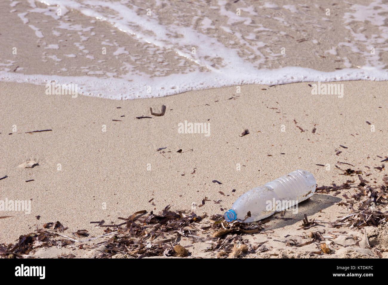 Empty plastic bottle lying on sandy beach at seaside - Stock Image