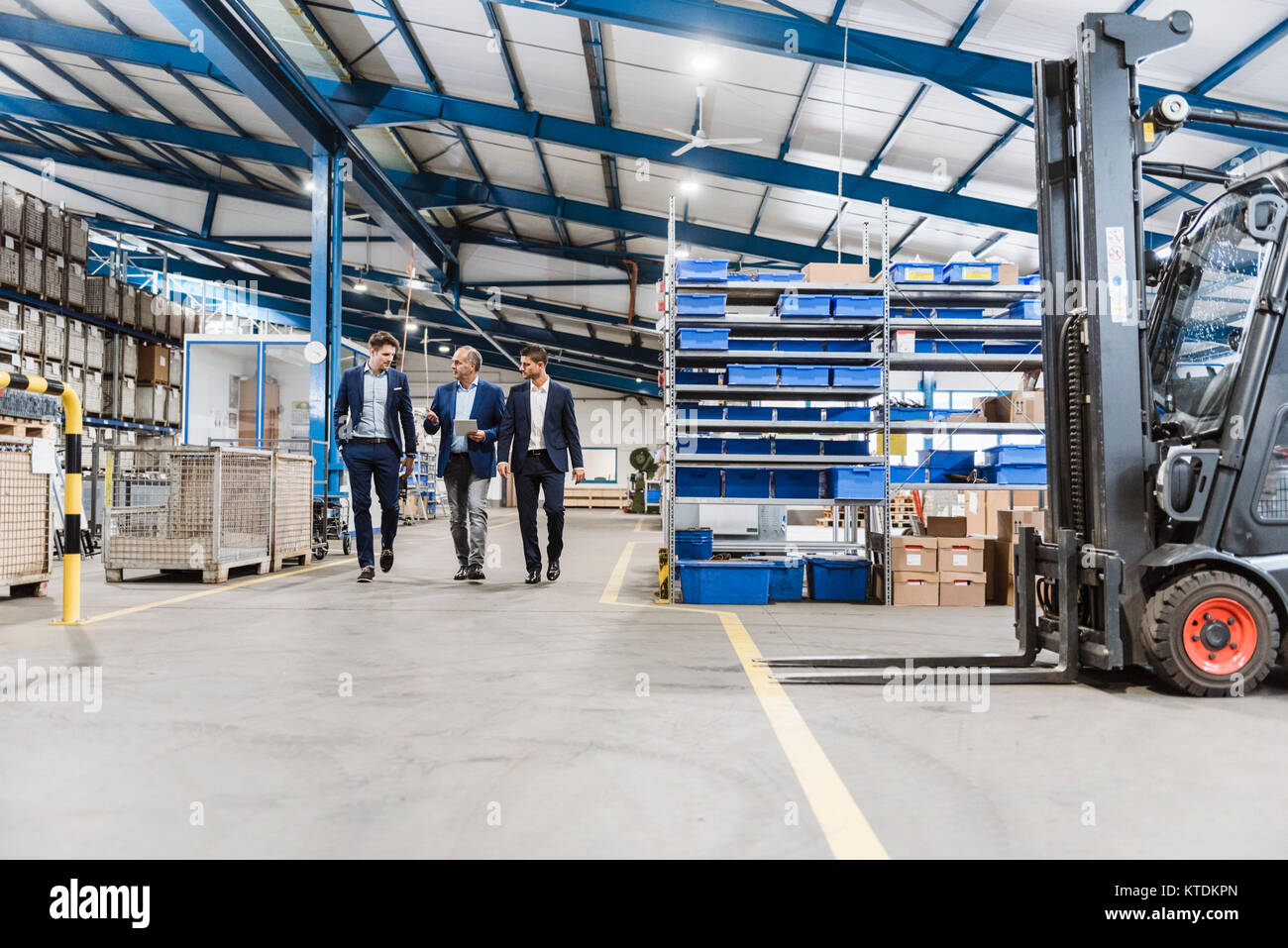 Three businessmen walking through shop floor, discussing decisions - Stock Image