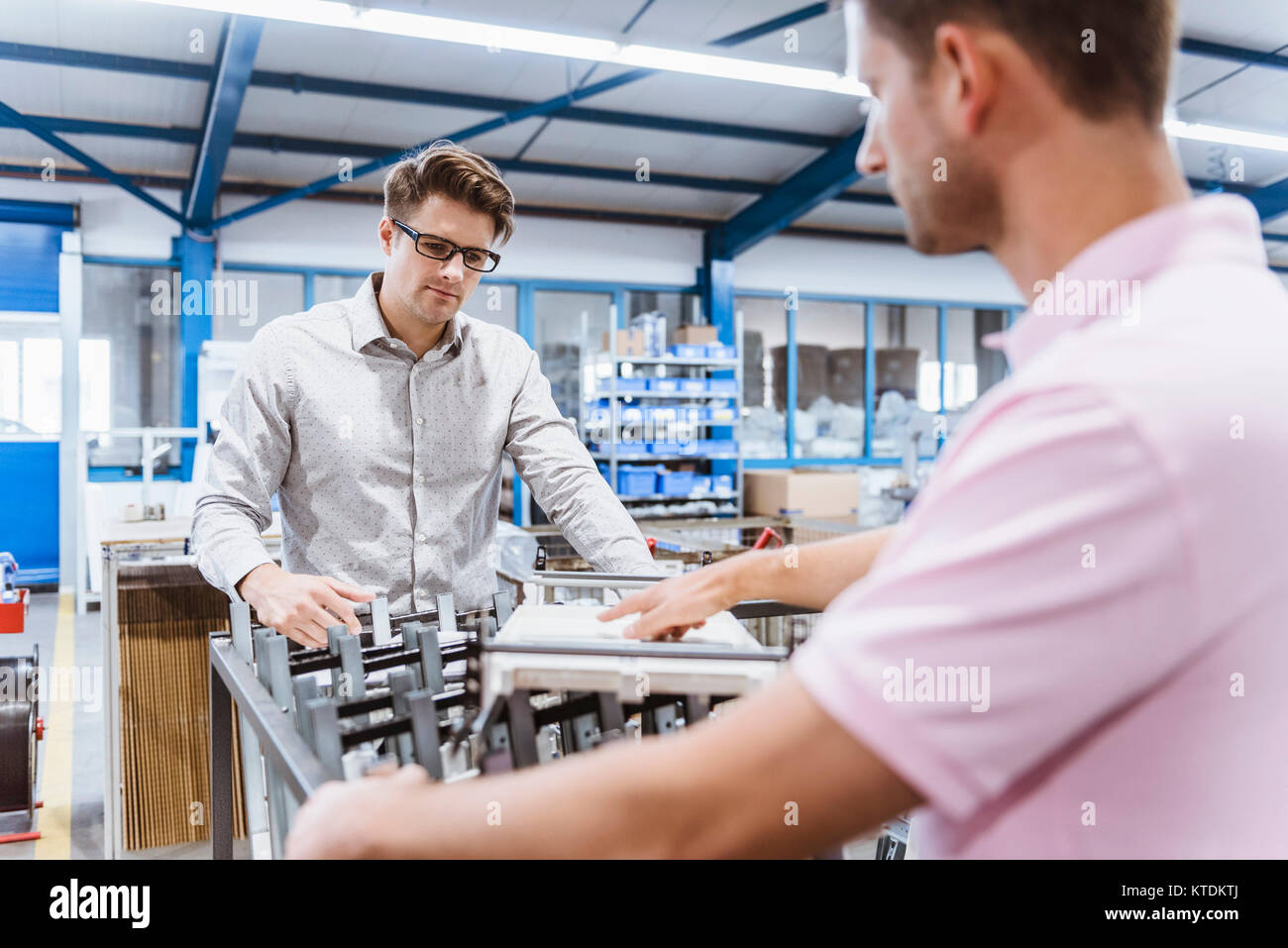 Employees In Shop Floor Checking Product Quality Stock Photo