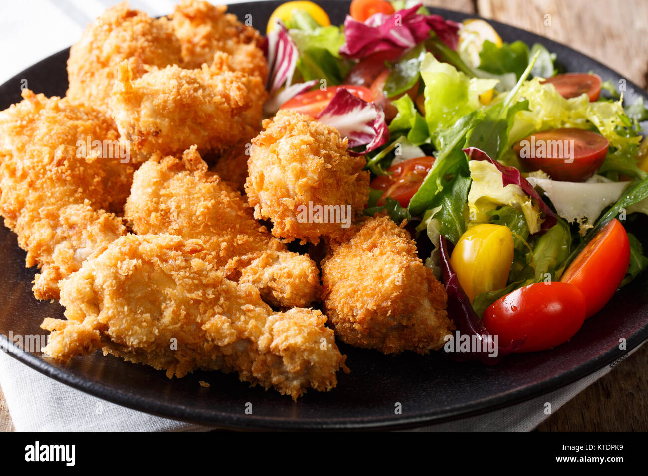 deep-fried chicken wings in breadcrumbs and fresh vegetable close-up on a plate. horizontal - Stock Image