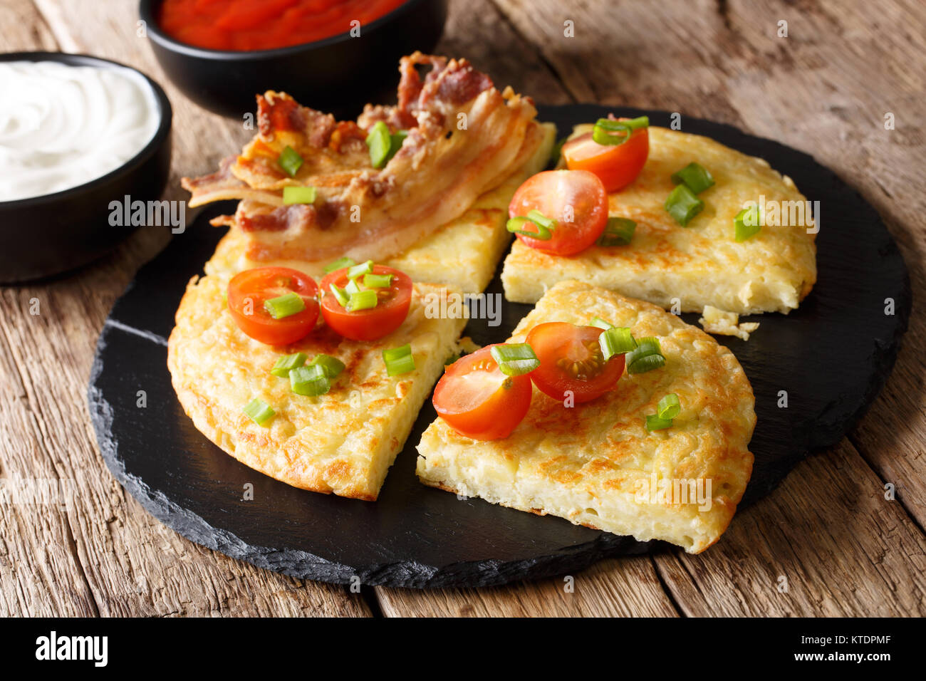 Potato Boxty with bacon, tomatoes, onions and sauce close-up on the table. horizontal - Stock Image