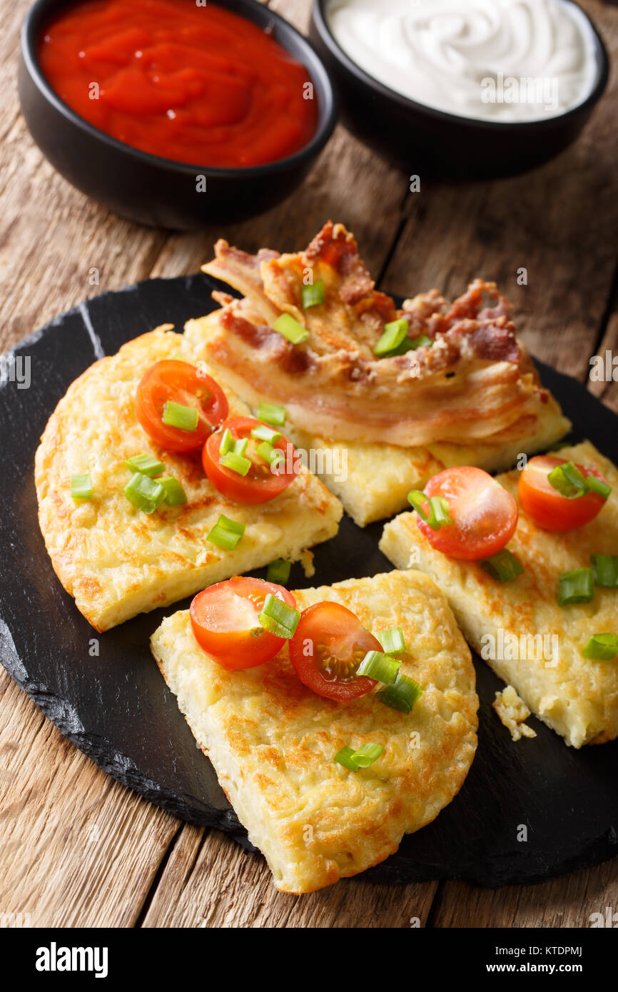 Irish Potato Boxty with bacon, tomato and sauce closeup on a plate. vertical - Stock Image