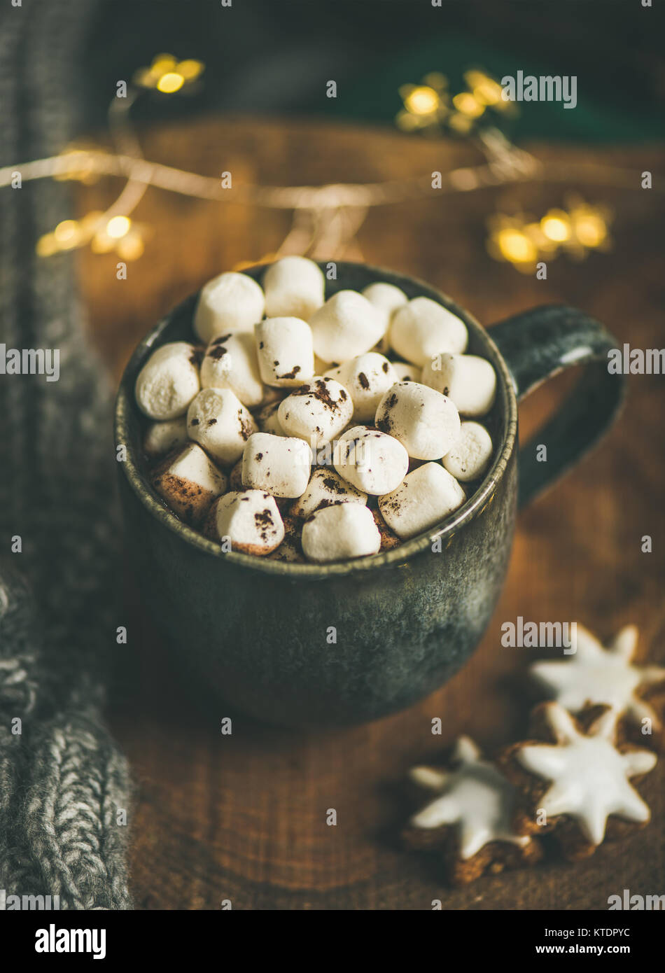 Christmas winter hot chocolate served with light garland and sweater - Stock Image