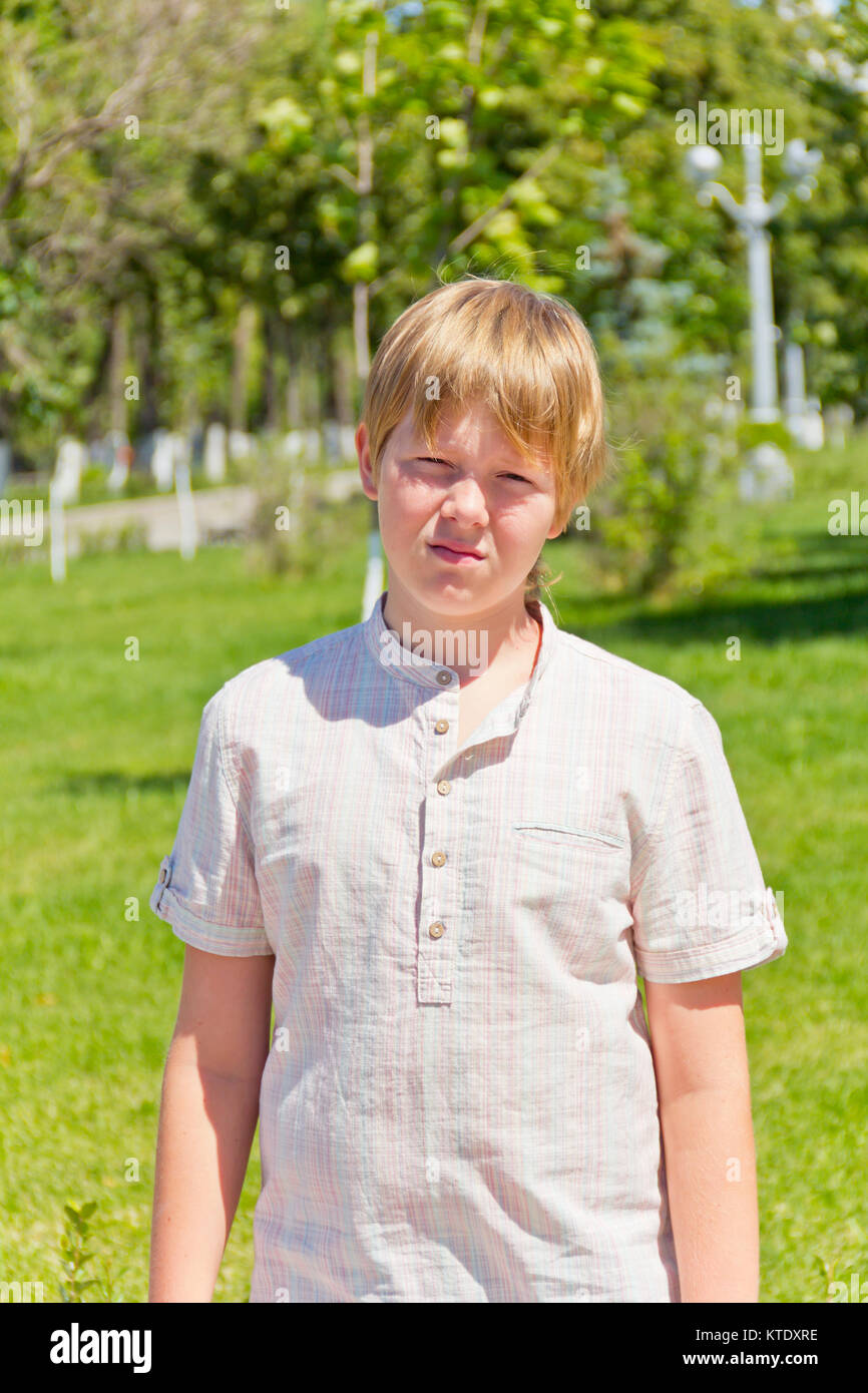 Portrait of dissatisfaction boy in white shirt outdoors - Stock Image