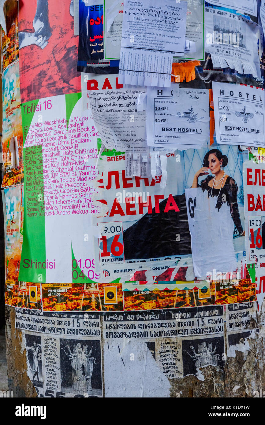 Colorful flyers and advertizing in different languages on a pillar in city center, Tbilisi, Georgia - Stock Image