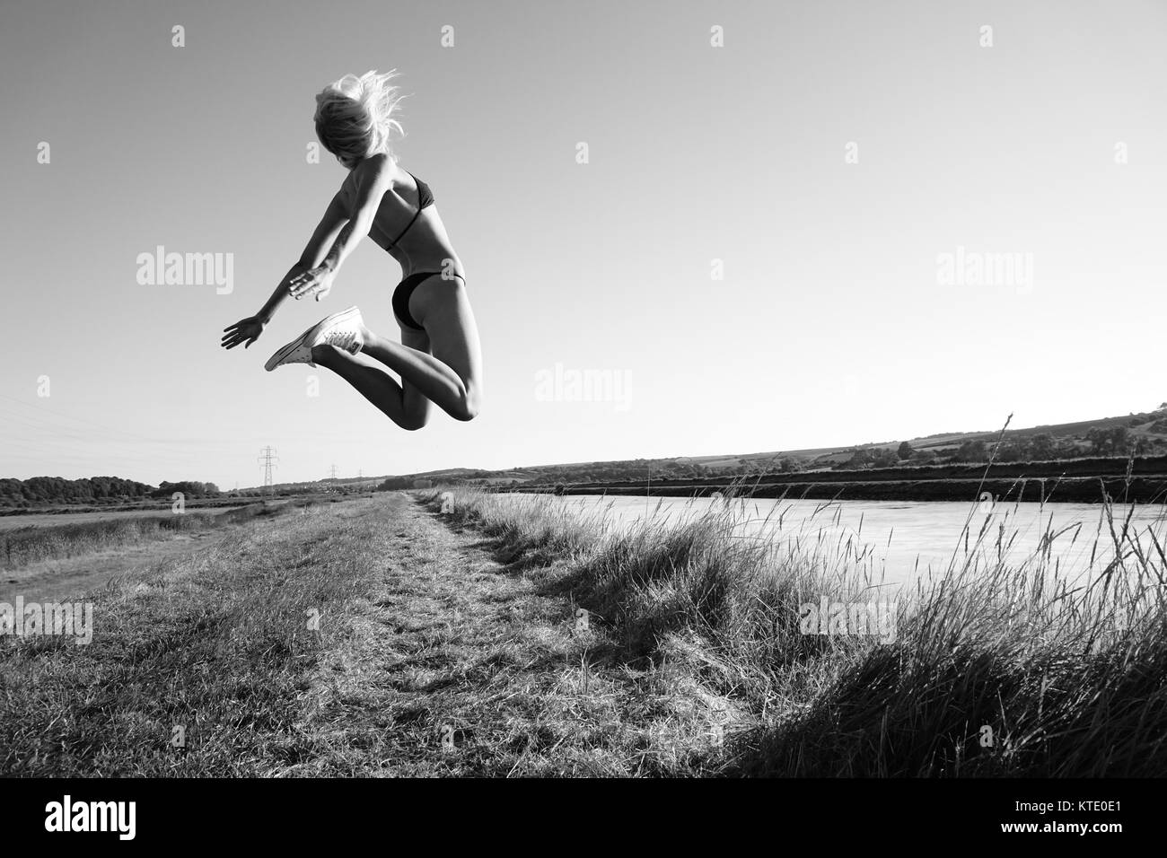 A young woman in bikini and running shoes jumps in the air - Stock Image