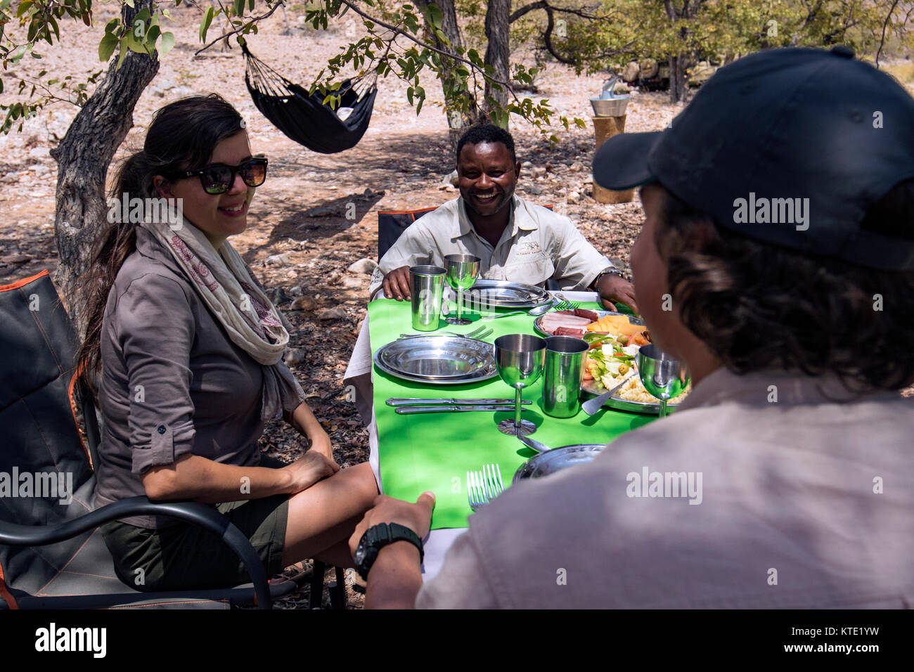 Couple enjoying picnic lunch at Huab Under Canvas, Damaraland, Namibia, Africa - Stock Image