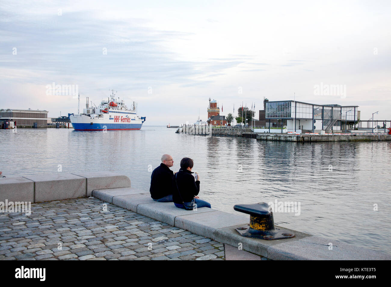 HELSINGBORG Skåne 2011 a couple sitting on the quay and enjoying a icecream with the ferries between Sweden - Stock Image