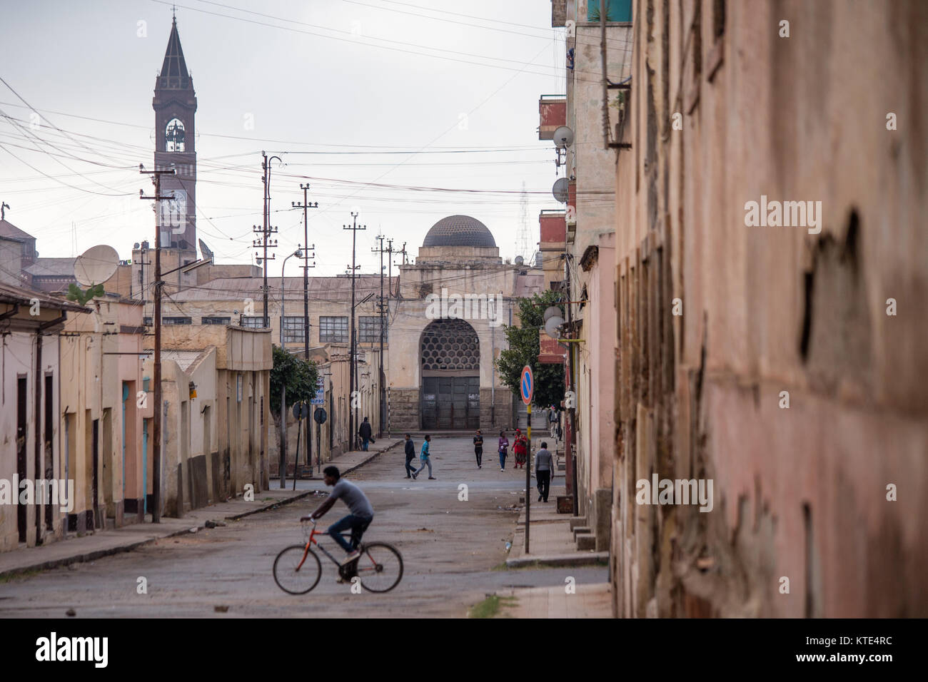 A man on a bicycle cross a street in the city of Asmara, Eritrea on the Horn of Africa. - Stock Image