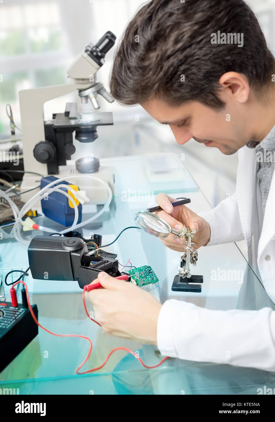 Young male tech or engineer repairs flash electronic unit in