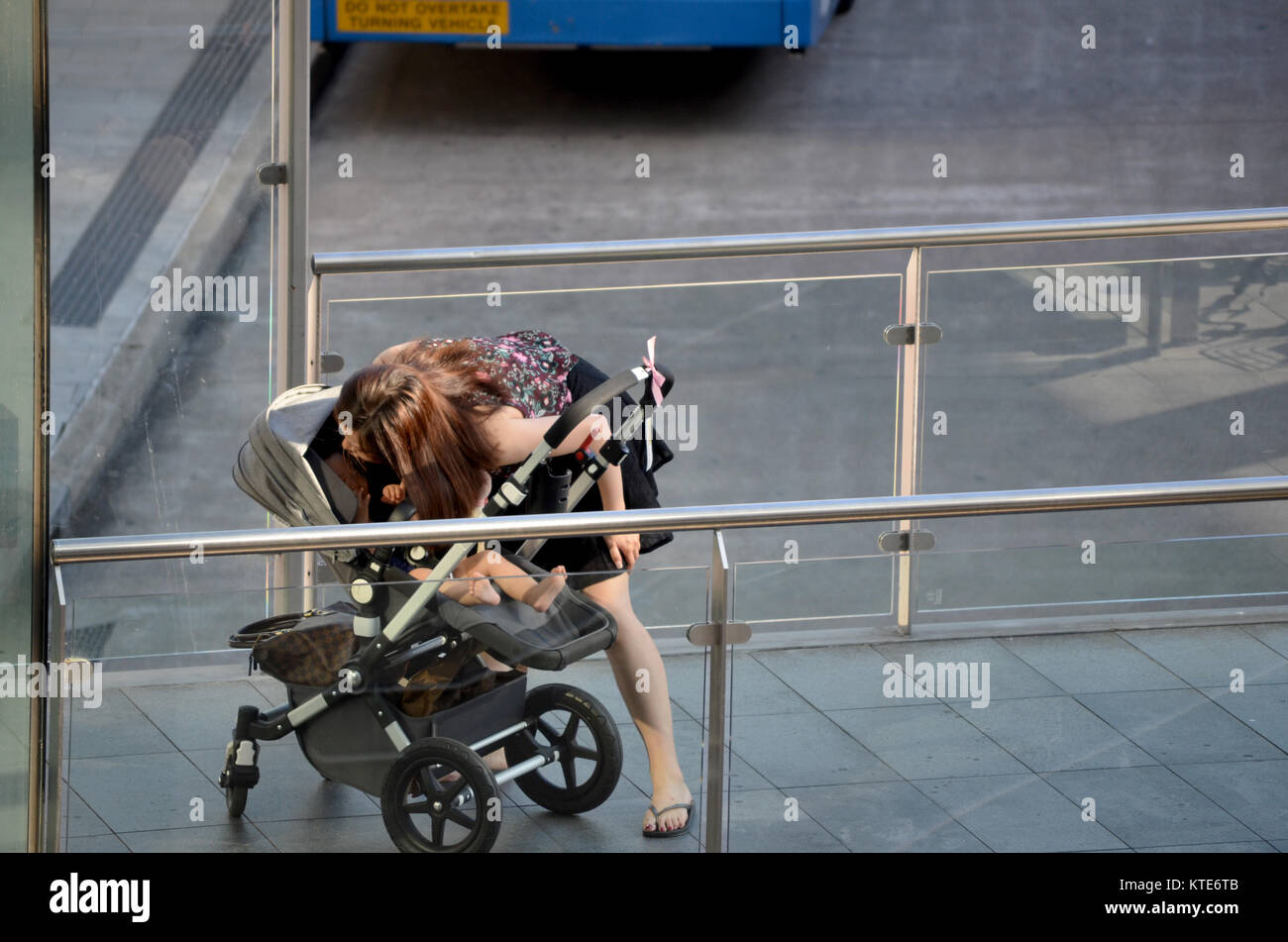 Young asian mother with child in pram at bus station - Stock Image