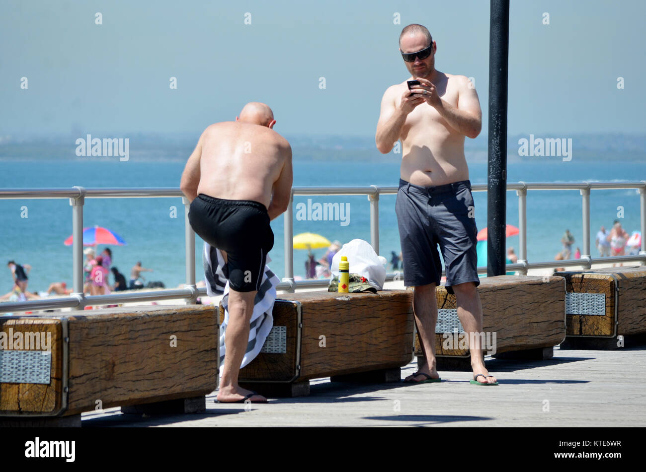 Cooling off. Two men after they have had a swim at the beach. - Stock Image