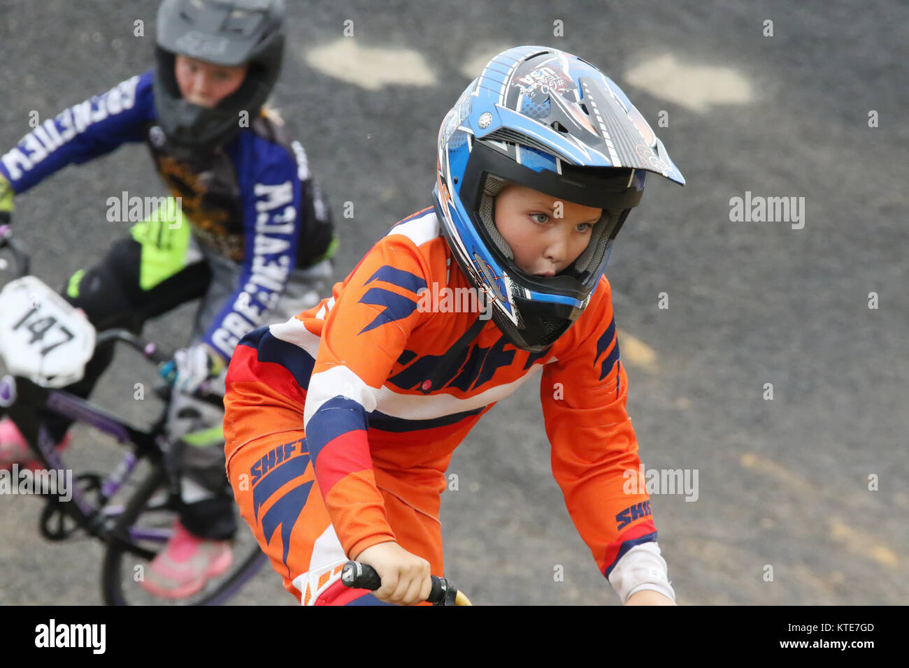 Preteen girl leads the boys in a race. Riders at Kettering BMX race night. BMX Track, Delco Park, Kettering, Dayton, - Stock Image