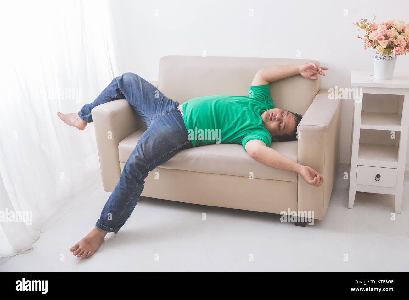 lazy Fat obese man sleeping on the couch - Stock Image