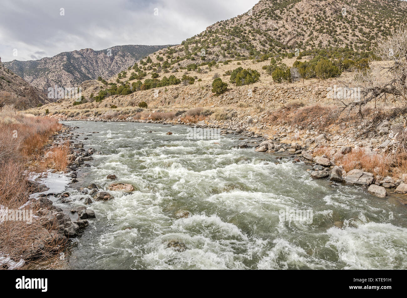 Arkansas River in Colorado running swiftly through the mountains on a winter day - Stock Image