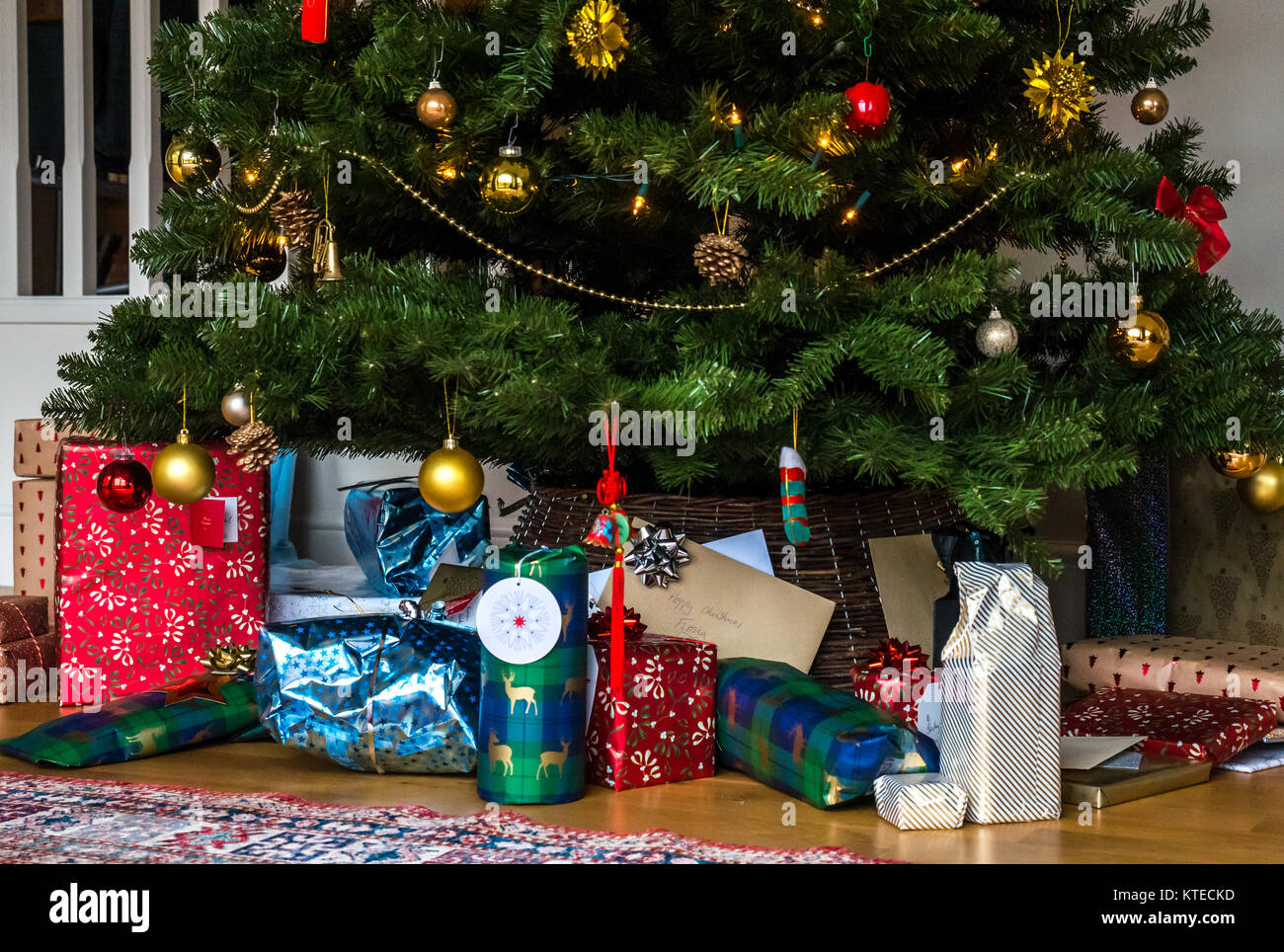 Wrapped Christmas presents under a Christmas tree in a family sitting room with a Persian rug - Stock Image