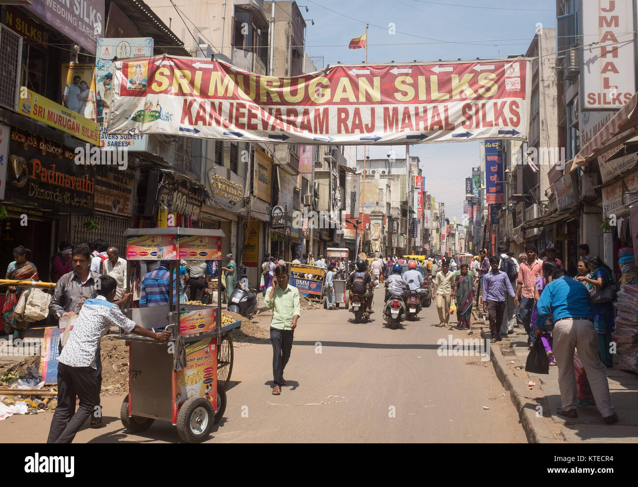 Crowd of people and vehicles moving on street, banner hanging over street in Bangalore, Bengaluru, Karnataka, India, - Stock Image