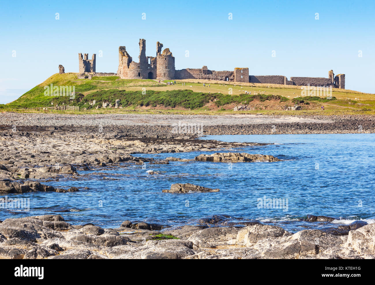 Dunstanburgh Castle is a 14th-century fortification on the coast of Northumberland in northern England, situated - Stock Image