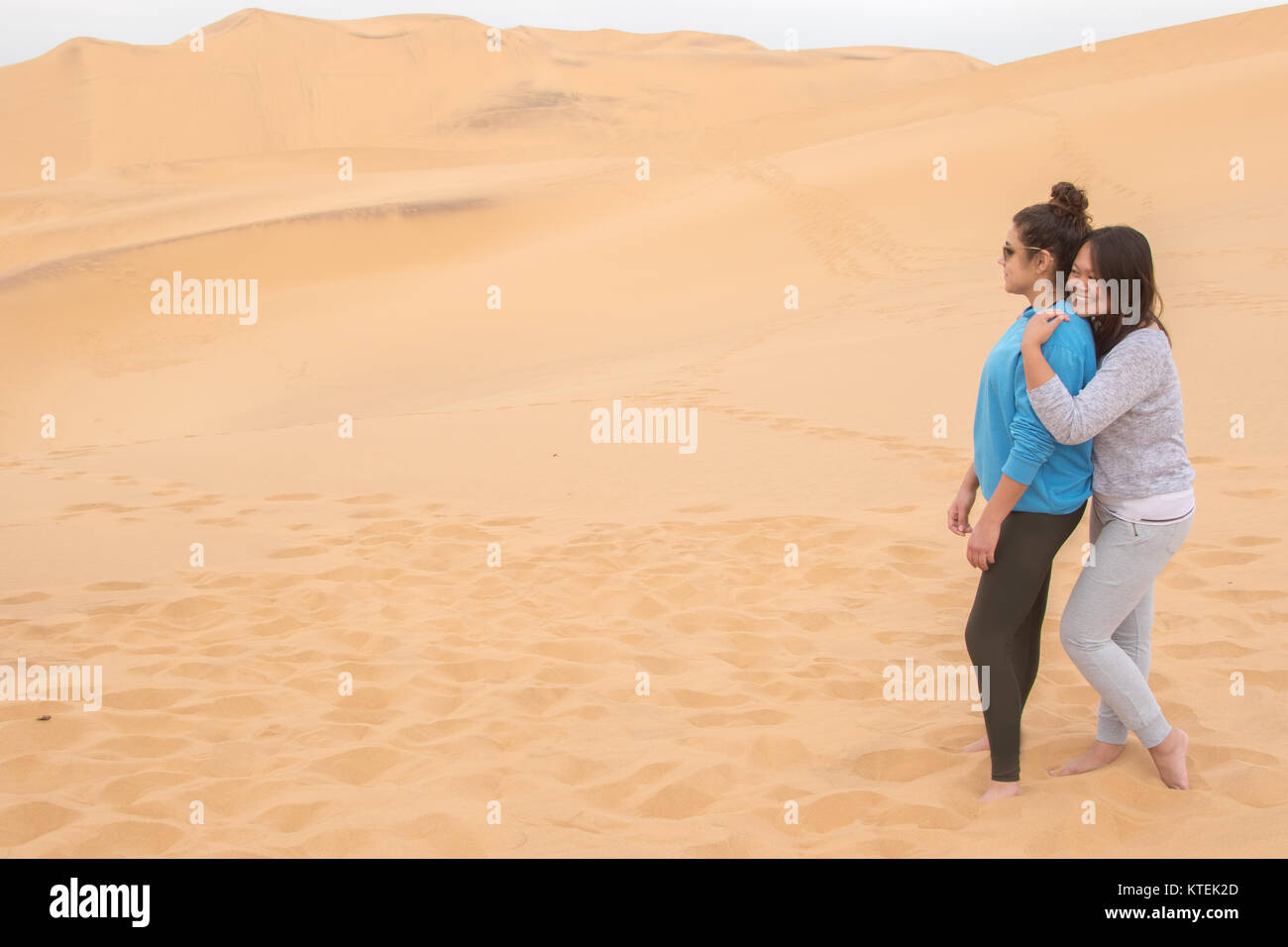 Two girls of different ethnicity having fun in the desert on Dune 7, Walvis Bay, Namibia Stock Photo