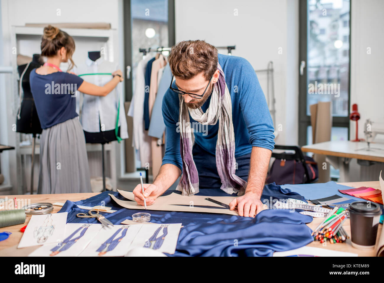 Couple Of Fashion Designers Working With Fabric And Clothing Sketches Stock Photo Alamy