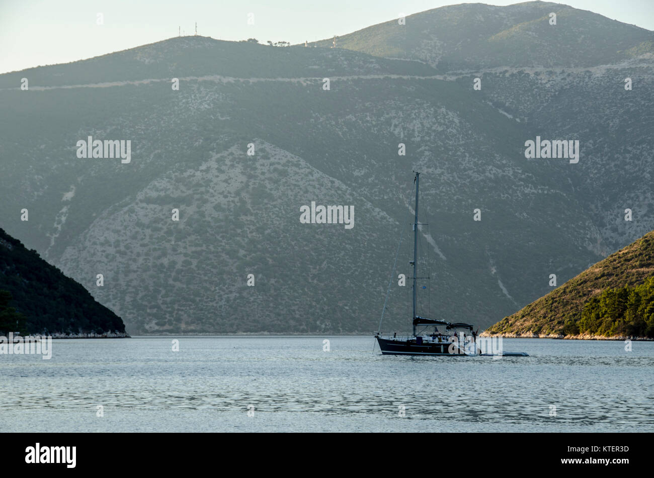 Sailboat sailing in the Ionian sea between the Ionian islands and their elevations nearly to the port of Vathy in Stock Photo