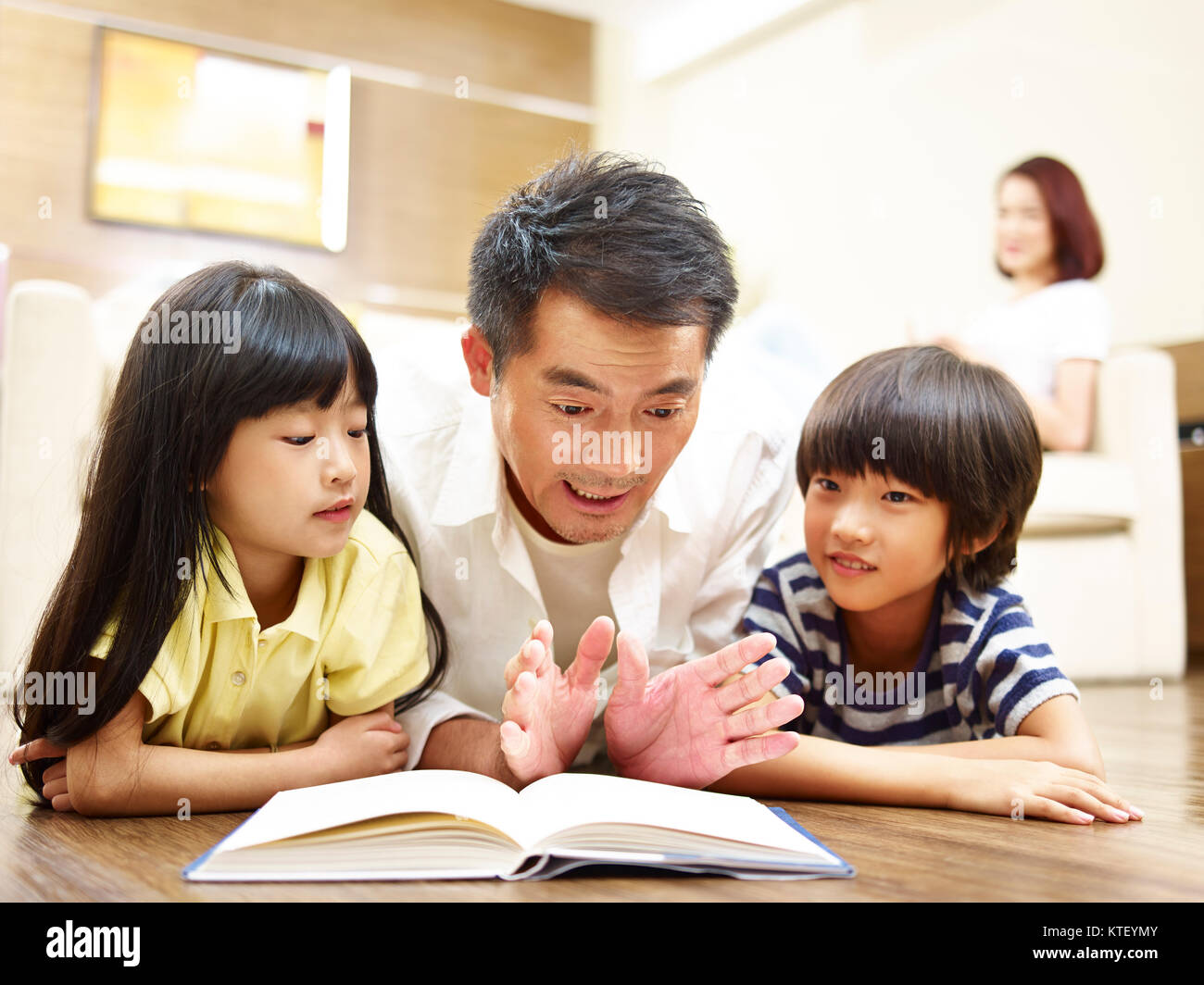 asian father and two children lying on front on floor reading book while mother watching in the background. - Stock Image