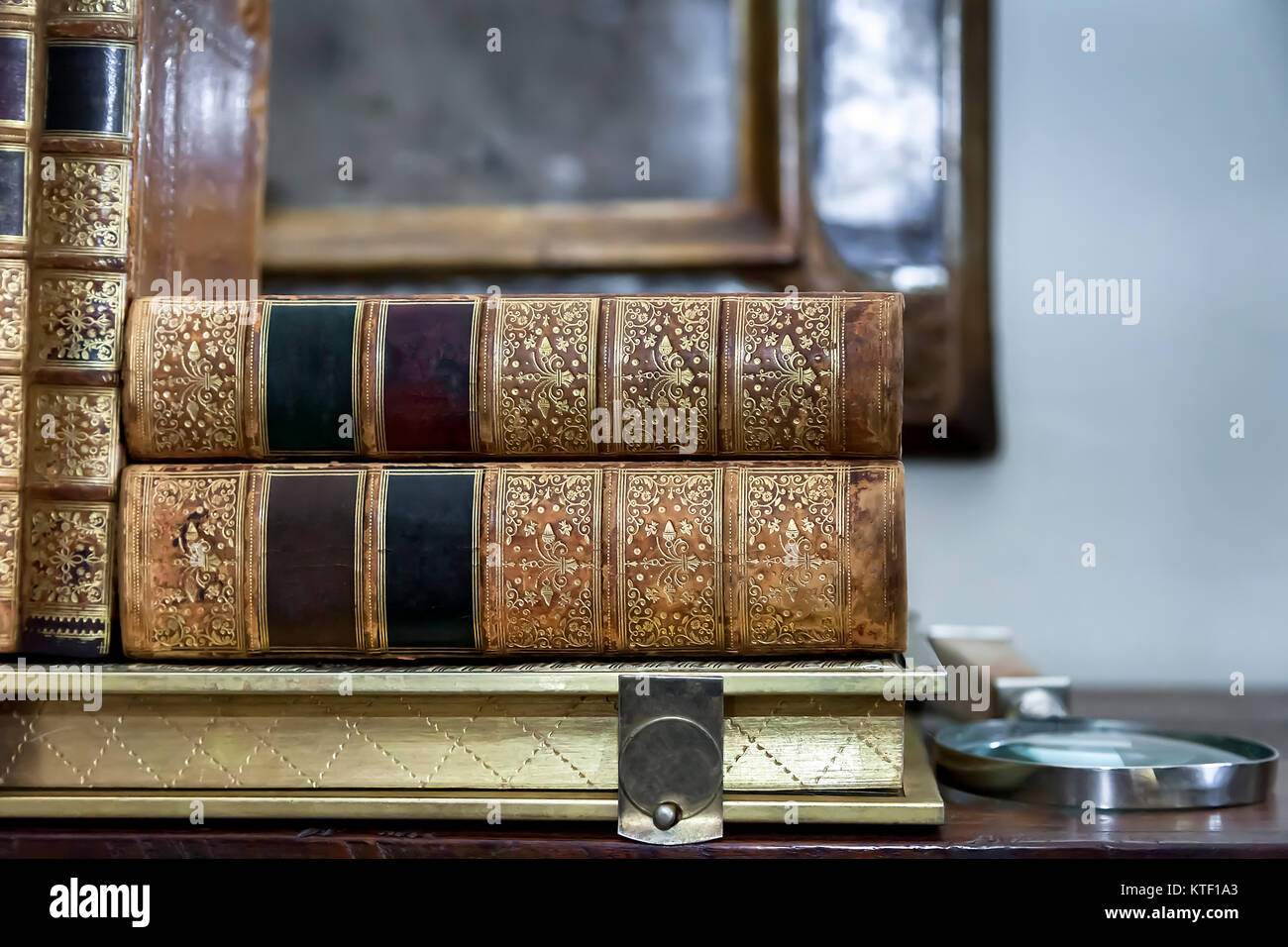 Antique Books. Vintage Antiquarian Books piled on wooden surface. Closeup. - Stock Image