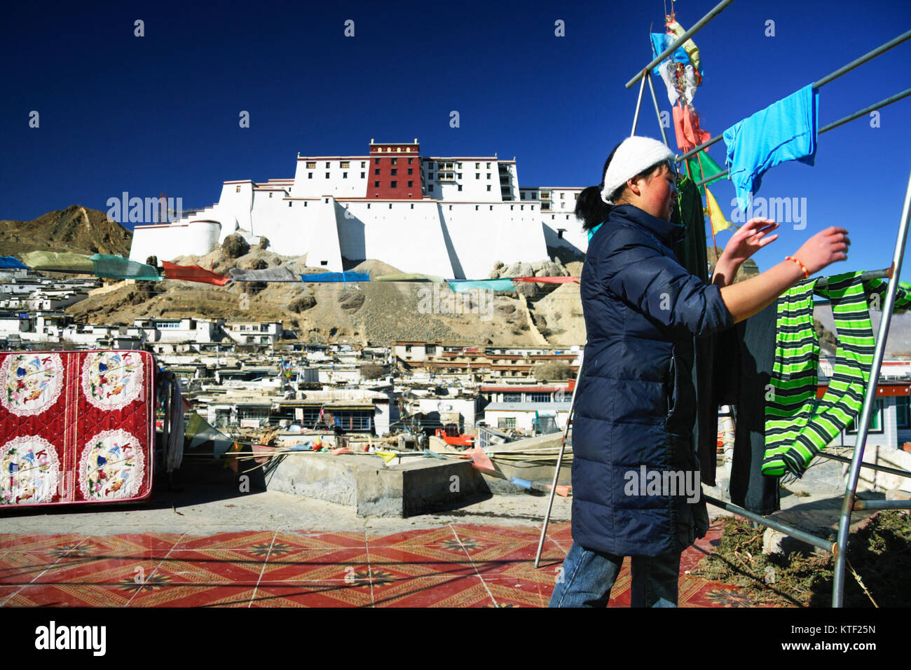 Tibetan woman doing laundry at a flat roof with the Samdruptse Dzong in background. Shigatse, Tibet - Stock Image