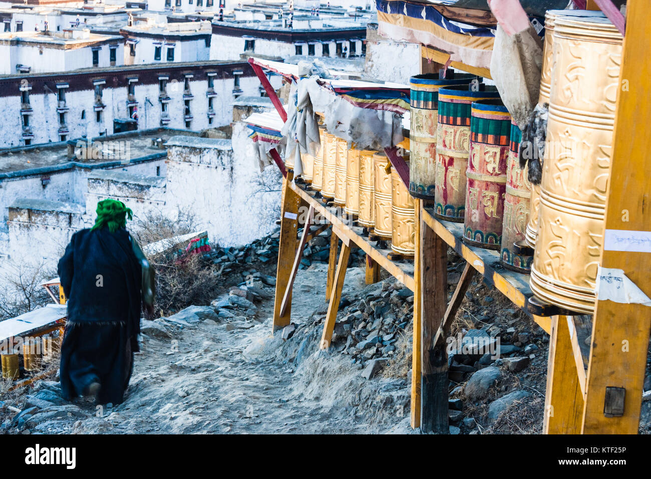Tibetan pilgrim and prayer wheels at Tashilhunpo Monastery, Shigatse, Tibet - Stock Image