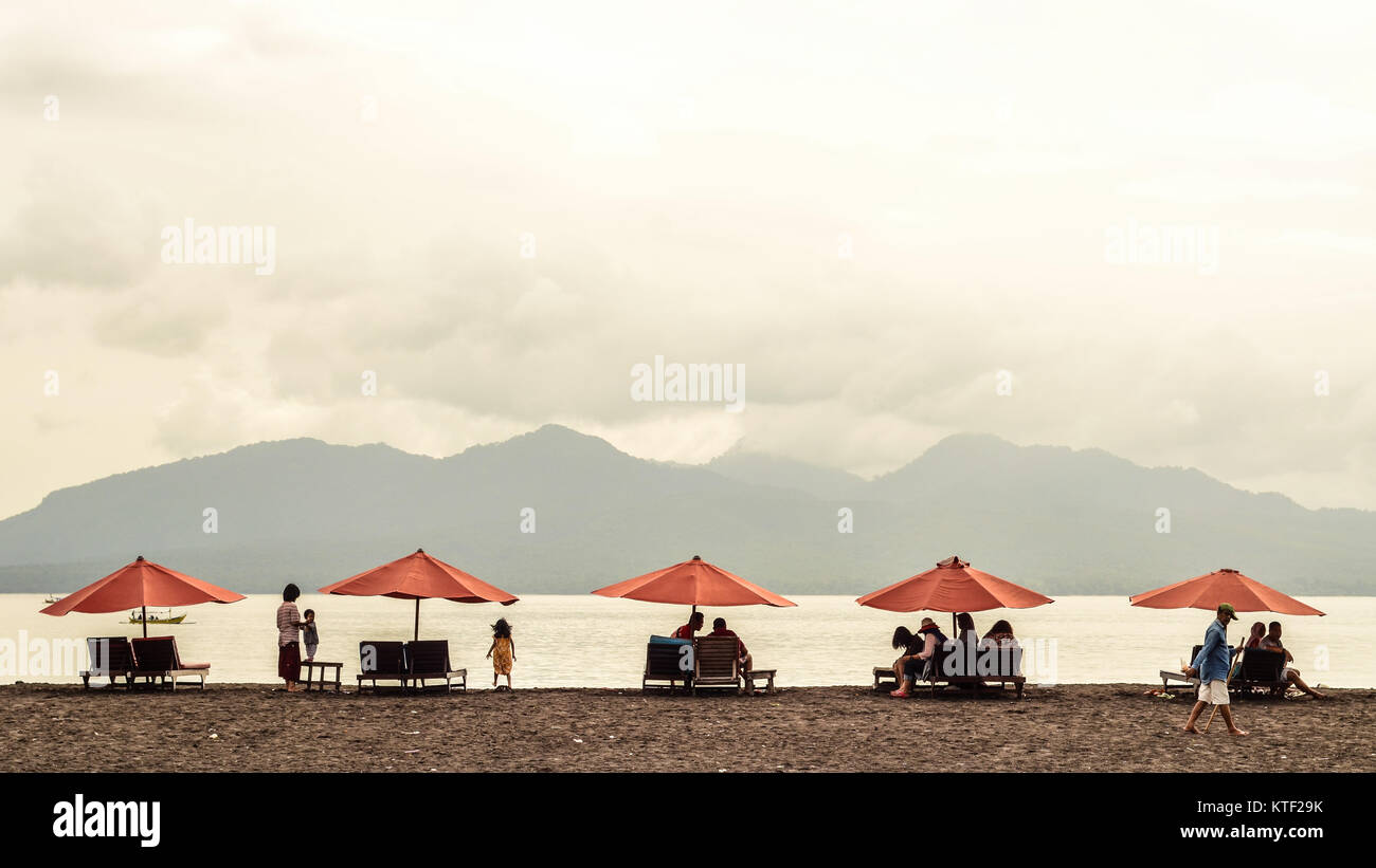 Traveller are taking shelter on orange umbrella in Pantai Boom Banyuwangi. The beach are facing to the east to the - Stock Image
