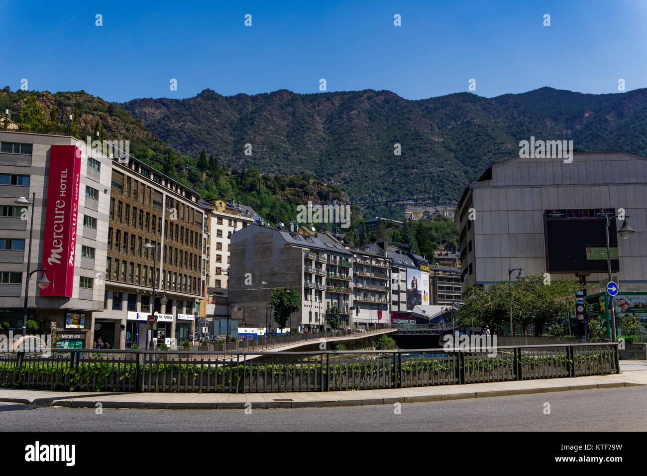Andorra la Vella, Andorra Hotel and houses on Gran Valira river. Local buildings by a green hill on the Andorran - Stock Image