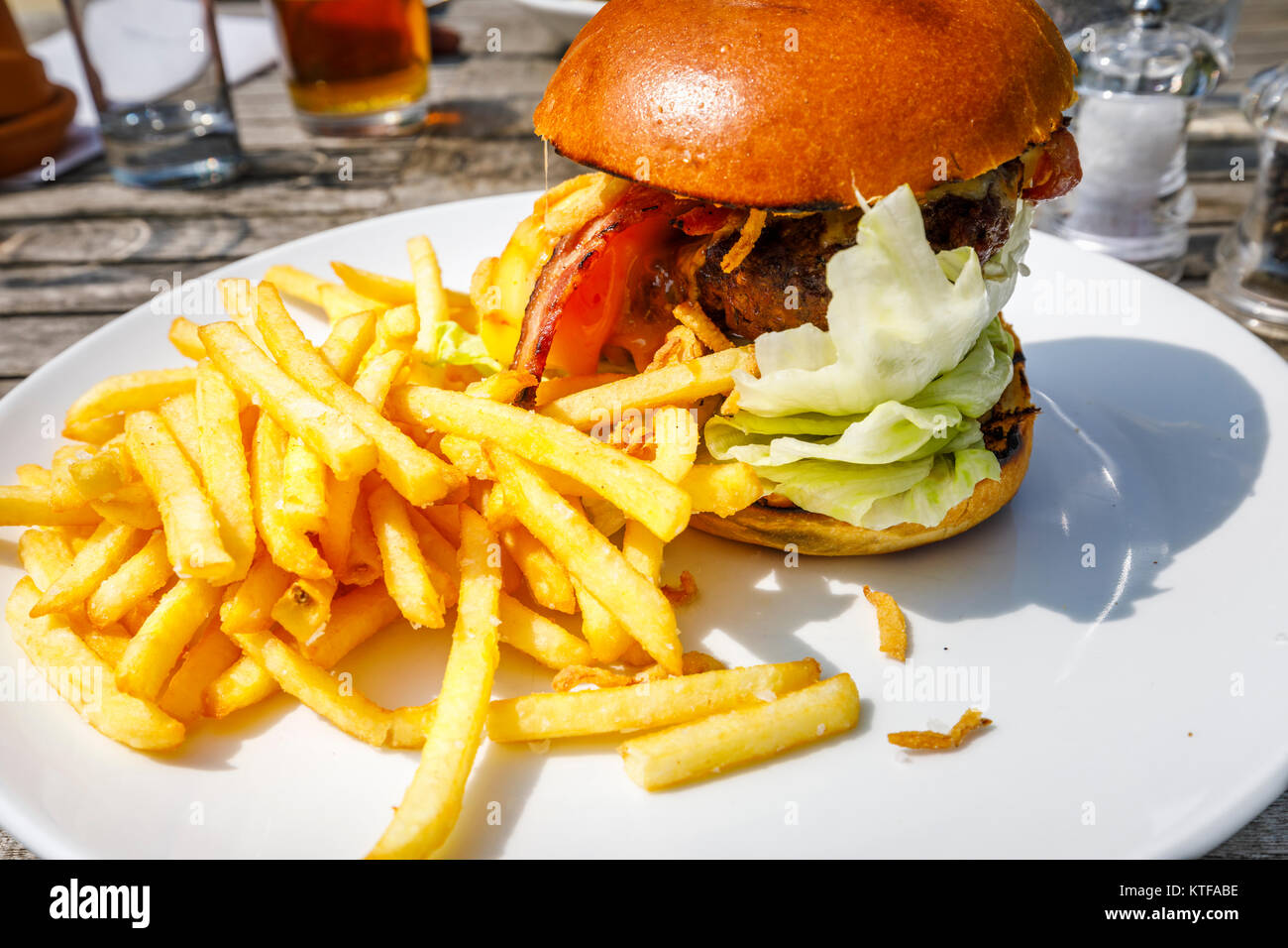 Obesity: Typical British pub food: a beefburger in a bun with cheese and bacon and a pile of golden French fries, - Stock Image