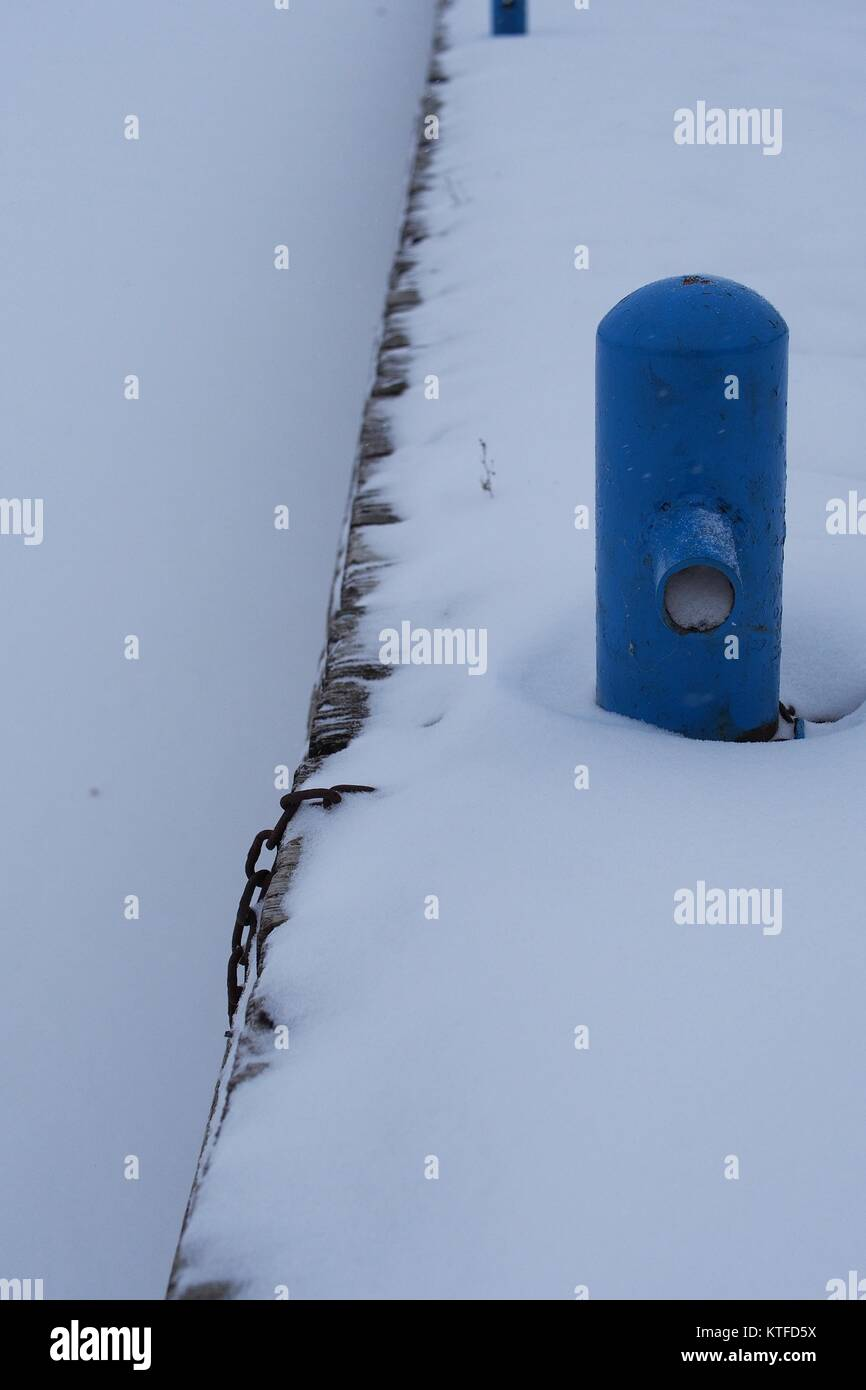 Snow covered blue mooring posts on the boardwalk at the north end of Dow's Lake, Ottawa, Ontario, Canada. - Stock Image